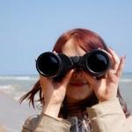 Girl with binocular at beach. — Stock Photo
