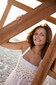 Portrait of young girl near wood on the beach — Stok fotoğraf