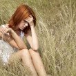 Sad red-haired girl at grass. - Stock Photo