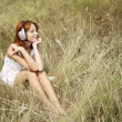 Beautiful red-haired girl at grass with headphones — Stock Photo #3662776