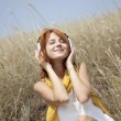Beautiful red-haired girl at grass with headphones — Stock Photo