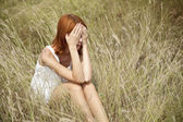 Sad red-haired girl at grass. — Stock Photo