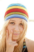 Beautiful young blonde girl in rastafarian hat — Stock Photo