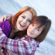 Closeup portrait of two happy girls on the beach — Stock Photo