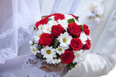 Bridegroom and bride holding beautiful red roses wedding flowers — Stock Photo