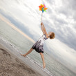 Blonde girl jumping with wind turbine at beach. — Stockfoto
