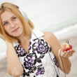 Young blonde girl with headphones and apple on the beach. — Stock Photo