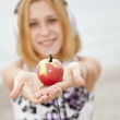 Young blonde girl with headphones and apple on the beach. — Stock Photo #3769625