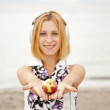 Young blonde girl with headphones and apple on the beach. — Stock Photo #3769630