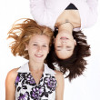 Stock Photo: Two funny girl lying on white background.