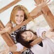Portrait of two girls near wood stairs on the beach. — Stock Photo #3769653