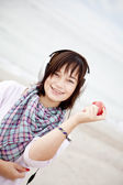 Young brunet girl with headphones and apple on the beach. — Stock Photo