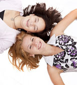 Two funny girl lying on white background. — Stock Photo
