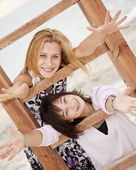 Portrait of two girls near wood stairs on the beach. — Stock Photo