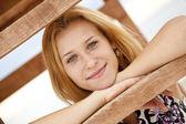 Prachtige blond meisje in de buurt van houten trap van buiten. — Stockfoto