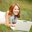 Young fashion girl with notebook lying at green grass — Stockfoto