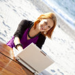 Royalty-Free Stock Photo: Portrait of red-haired girl with laptop at beach.