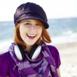 Portrait of red-haired girl with headphone on the beach. - Stock Photo
