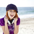 Portrait of red-haired girl with headphone on the beach. — Stock Photo #3790660