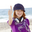 Red-haired girl with headphone on the beach. — Stock Photo #3790665