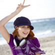 Red-haired girl with headphone on the beach. — Stock Photo #3790666