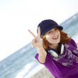 Red-haired girl with headphone on the beach. — Stock Photo #3790667