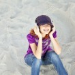 Portrait of red-haired girl with headphone on the beach. — Stock Photo #3790672