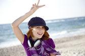 Garota ruiva com fone de ouvido na praia. — Foto Stock