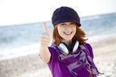 Roodharige meisje met hoofdtelefoon op het strand. — Stockfoto