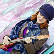 Closeup portrait of a happy young girl with guitar and graffiti - Foto Stock