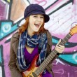 Closeup portrait of a happy young girl with guitar and graffiti — Stock Photo