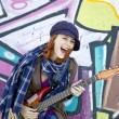 Closeup portrait of a happy young girl with guitar and graffiti - Stockfoto
