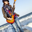Young red-haired girl play on guitar at windy day. — Stock Photo #3808192