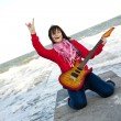 Young brunet girl play on guitar at sea pier in wind day. — Stock Photo #3808222