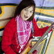 Closeup portrait of a happy young girl with guitar and graffiti — Stock Photo #3808245