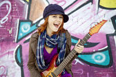 Closeup portrait of a happy young girl with guitar and graffiti — ストック写真