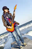 Young red-haired girl play on guitar at windy day. — Стоковое фото