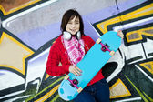 Closeup portrait of a happy young girl with skateboard and graff — Stock Photo