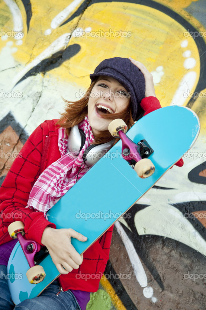 Closeup portrait of a happy young girl with skateboard and graffiti on background — Stock Photo #3808259