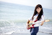Pretty young woman with guitar on beach — Stock Photo