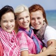 Three hugging girls at the beach. — Stock Photo