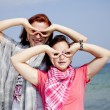 Royalty-Free Stock Photo: Two girlfriends at the beach show binocular