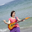 Young brunet girl with guitar on the beach. — Stock Photo