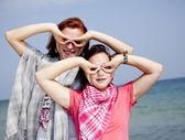 在海滩上的两个女朋友显示双目 — 图库照片