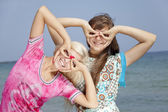 Two girlfriends at the beach show binocular — Stock Photo