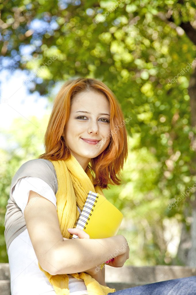 Red-haired student girl with notebook sitting at outdoor. — Stock Photo #3875534