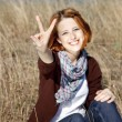 Portrait of red-haired on autumn grass which show hand V symbol. — Stock Photo