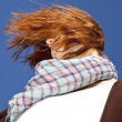 Portrait of red-haired girl with scarf on blue background. — Stock Photo