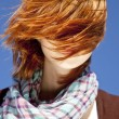 Royalty-Free Stock Photo: Portrait of red-haired girl with scarf on blue background.