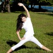 Beautiful young brunet yoga girl on green grass in park. — Foto de Stock